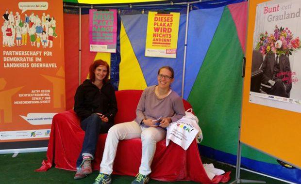 Susann Reissig und Juliane Lang sitzen vor dem gemeinsamen Messestand des Kreisjugendring Oberhavel und der Partnerschaft für Demokratie Oberhavel