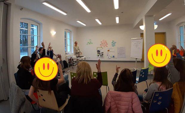 Ein Bild vom Jugendforum 2019 zeigt Teilnehmer*innen, die sich per Handzeichen an einer Diskussion beteiligen.