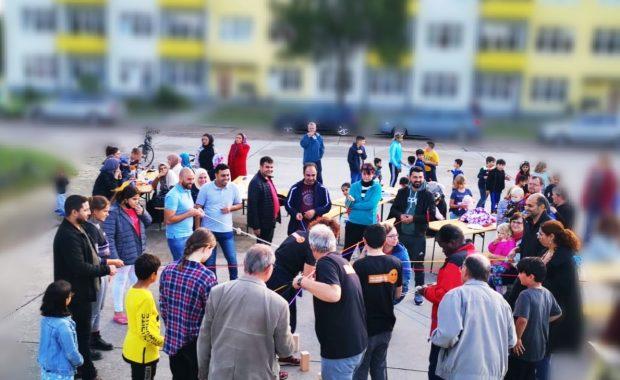 Das Bild zeigt eine vielfältige Gruppe an Menschen, die gemeinsam ein Spiel spielen.