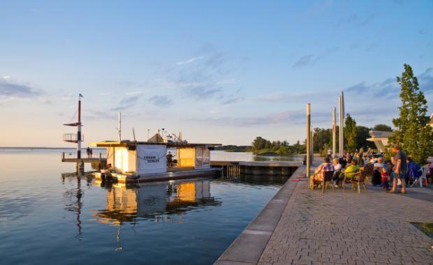 Das Theaterschiff der Traumschüff geG mit Publikum im Sonnenuntergang