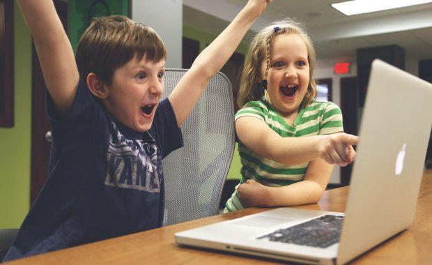 Zwei begeisterte Kinder, die vor einem Laptop sitzen. Zugang zur Bildung für alle. Spendet Laptops.